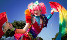 Stilt walker dressed in rainbow outfit smiling at camera