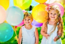 two children holding balloons and smiling