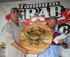 2 men holding crab trophie